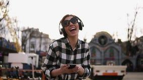 Música que escucha de la chica joven bonita en auriculares, el salto y el baile Forma de vida feliz afuera Cámara lenta metrajes
