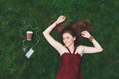 Música que escucha de la chica joven bonita en los auriculares que mienten en hierba Foto de archivo