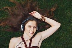 Música que escucha de la chica joven bonita en los auriculares que mienten en hierba Fotografía de archivo libre de regalías