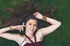 Música que escucha de la chica joven bonita en los auriculares que mienten en hierba Imagen de archivo