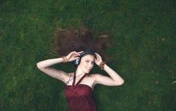 Música que escucha de la chica joven bonita en los auriculares que mienten en hierba Imágenes de archivo libres de regalías