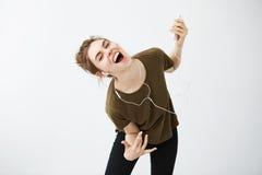 Música que escucha de la chica joven del canto alegre loco del baile en auriculares sobre el fondo blanco Imágenes de archivo libres de regalías