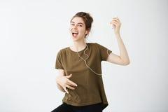 Música que escucha de la chica joven del canto alegre loco del baile en auriculares sobre el fondo blanco Foto de archivo