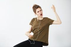Música que escucha de la chica joven del canto alegre loco del baile en auriculares sobre el fondo blanco Fotos de archivo libres de regalías