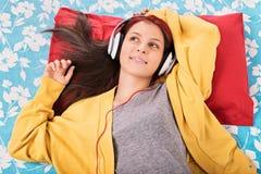 Música que escucha de la chica joven en su cama Foto de archivo