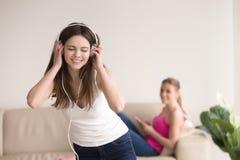 Música que escucha de la chica joven y su novia que se relajan en el sofá Fotografía de archivo libre de regalías