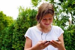 Música que escucha de la colegiala joven del adolescente en su smartphone Imagen de archivo