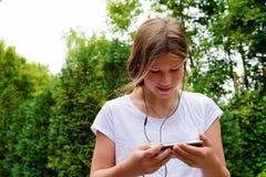 Música que escucha de la colegiala joven del adolescente en su smartphone Imagen de archivo libre de regalías