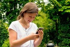 Música que escucha de la colegiala joven del adolescente en su smartphone Fotografía de archivo