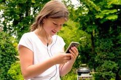 Música que escucha de la colegiala joven del adolescente en su smartphone Imagenes de archivo