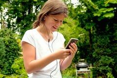 Música que escucha de la colegiala joven del adolescente en su smartphone Imágenes de archivo libres de regalías