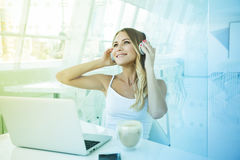 Música que escucha de la empresaria hermosa joven en auriculares en o Foto de archivo libre de regalías