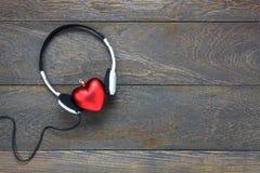 música que escucha de la forma roja del corazón con los auriculares en la madera Fotografía de archivo libre de regalías