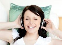 Música que escucha de la muchacha adolescente alegre que miente en un sofá Imagen de archivo