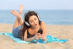 Música que escucha de la muchacha adolescente y canto en la playa Imagen de archivo libre de regalías