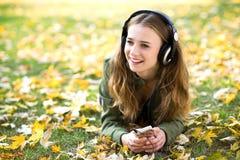 Música que escucha de la muchacha al aire libre Foto de archivo libre de regalías