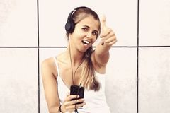 Música que escucha de la muchacha atractiva joven con el auricular y las demostraciones t Foto de archivo libre de regalías