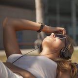 Música que escucha de la muchacha atractiva joven feliz con el auricular Fotos de archivo