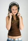 Música que escucha de la muchacha bonita joven con los auriculares Fotos de archivo libres de regalías