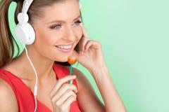 Música que escucha de la muchacha colorida divertida en fondo verde Mujer atractiva que escucha la música en los auriculares y qu Imágenes de archivo libres de regalías