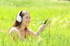 Música que escucha de la muchacha con los auriculares y el teléfono elegante en un campo Fotos de archivo libres de regalías