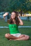 Música que escucha de la muchacha con los auriculares y sostener un smartphone Imagen de archivo libre de regalías