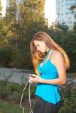 Música que escucha de la muchacha con los auriculares y sostener un smartphone Foto de archivo libre de regalías