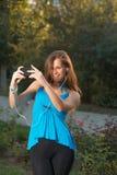 Música que escucha de la muchacha con los auriculares y sostener un smartphone Fotos de archivo