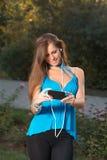 Música que escucha de la muchacha con los auriculares y sostener un smartphone Fotos de archivo libres de regalías
