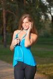 Música que escucha de la muchacha con los auriculares y sostener un smartphone Fotografía de archivo