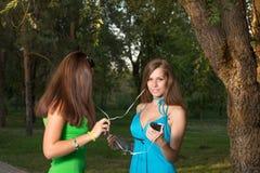 Música que escucha de la muchacha con los auriculares y sostener un smartphone imagen de archivo