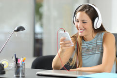 Música que escucha de la muchacha con smartphone y los auriculares Fotografía de archivo libre de regalías