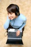 Música que escucha de la muchacha de la computadora portátil Imagen de archivo