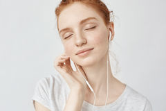 Música que escucha de la muchacha del pelirrojo en auriculares con los ojos cerrados Imágenes de archivo libres de regalías