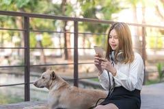 Música que escucha de la muchacha en línea con los auriculares Fotografía de archivo