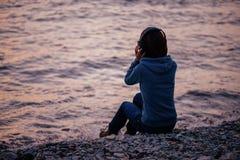 Música que escucha de la muchacha en la playa en puesta del sol Imagen de archivo libre de regalías