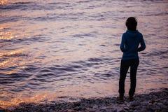 Música que escucha de la muchacha en la playa y la puesta del sol del goce Imagen de archivo libre de regalías