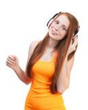 Música que escucha de la muchacha en los auriculares Aislado en el backgroun blanco Imagenes de archivo