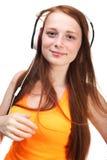 Música que escucha de la muchacha en los auriculares Aislado en el backgroun blanco Foto de archivo libre de regalías