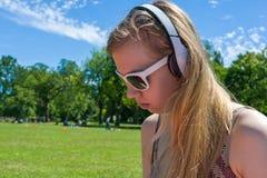 Música que escucha de la muchacha en parque Foto de archivo libre de regalías