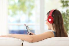 Música que escucha de la muchacha en un sofá en casa Imágenes de archivo libres de regalías