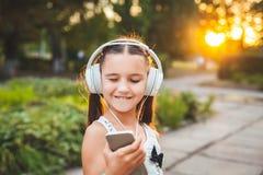 Música que escucha de la muchacha feliz en el teléfono Imagen de archivo libre de regalías