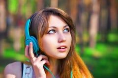 Música que escucha de la muchacha hermosa con los auriculares Foto de archivo libre de regalías