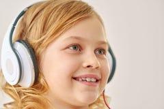 Música que escucha de la muchacha linda en los auriculares Fotos de archivo
