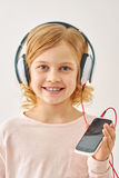 Música que escucha de la muchacha linda en los auriculares Fotografía de archivo
