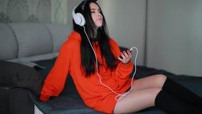 Música que escucha de la muchacha linda en sofá de los auriculares en casa metrajes