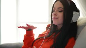 Música que escucha de la muchacha linda en sofá de los auriculares en casa almacen de video