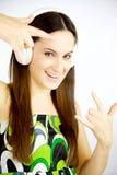 Música que escucha de la muchacha linda feliz con los auriculares que sonríen mirando la cámara Foto de archivo libre de regalías