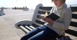 Música que escucha de la muchacha mientras que lee un libro en la playa 4k almacen de video