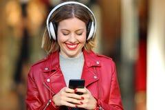 Música que escucha de la muchacha de la moda en una alameda Imagen de archivo libre de regalías